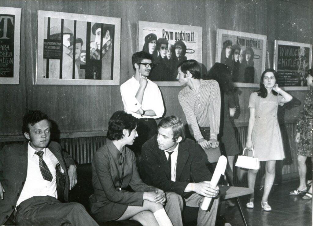 Na czarno-białej fotografii widać wnętrze Ikonosfery. Na ścianie klasyczne plakaty filmowe RZYM GODZINA 11, NEAPOLITAŃCZYCY W MEDIOLANIE. Na kanapie siedzą trzy osoby, elegancko ubrane. Za nimi stoją cztery osoby.