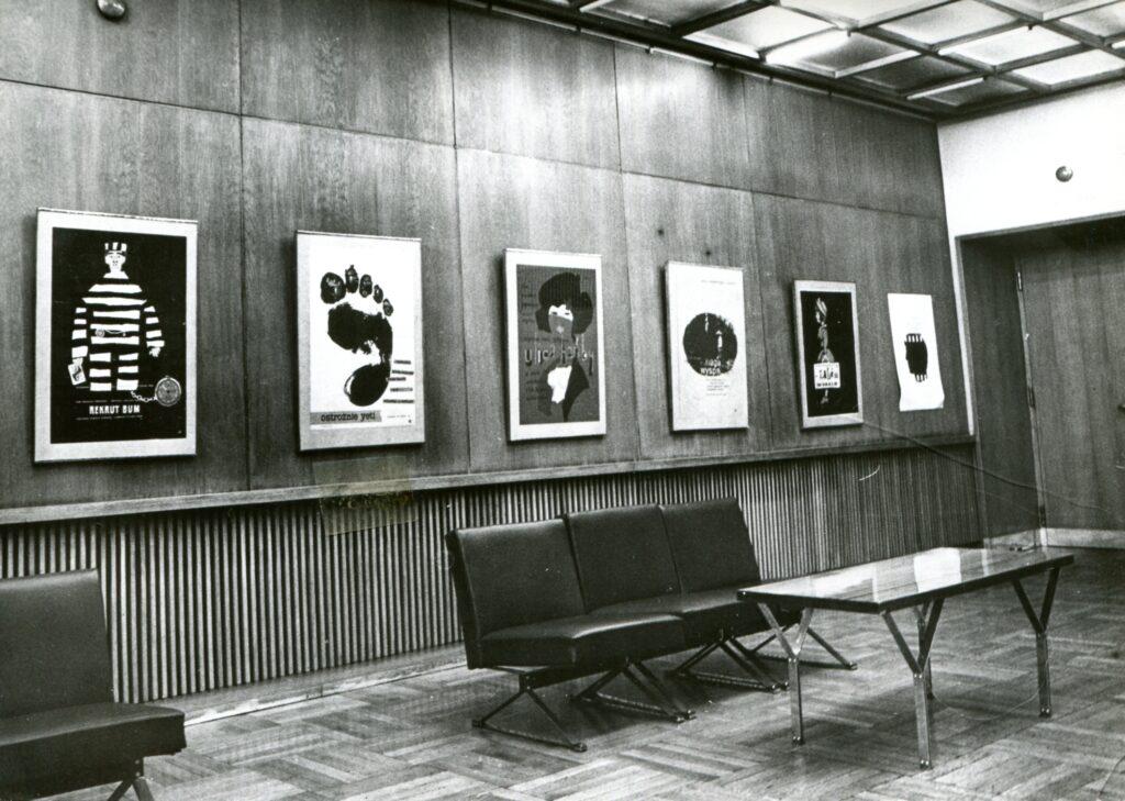 Wnętrze Ikonosfery. Na drewnianej boazerii sześć klasycznych plakatów filmowych. Na drewnianej posadzce czarne skórzane kanapy, stolik kawowy.