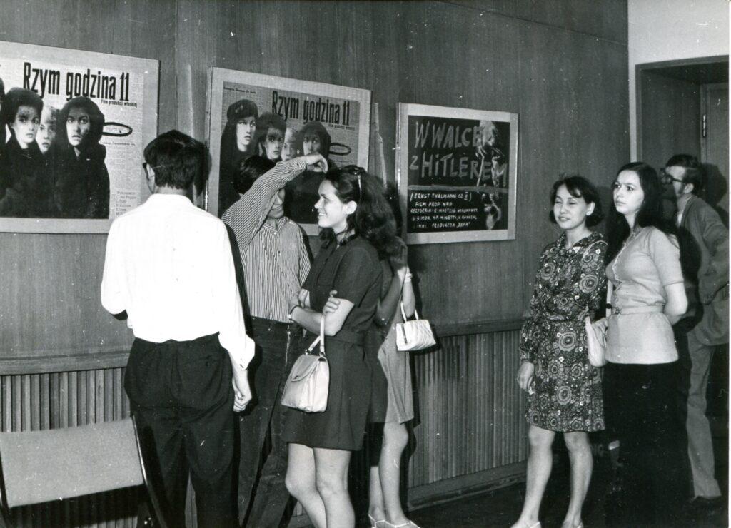 Na czarno-białej fotografii widać grono elegancko ubranych ludzi odwiedzających Ikonosferę. Na ścianie wiszą klasyczne plakaty filmowe, między innymi Rzym godzina 11.