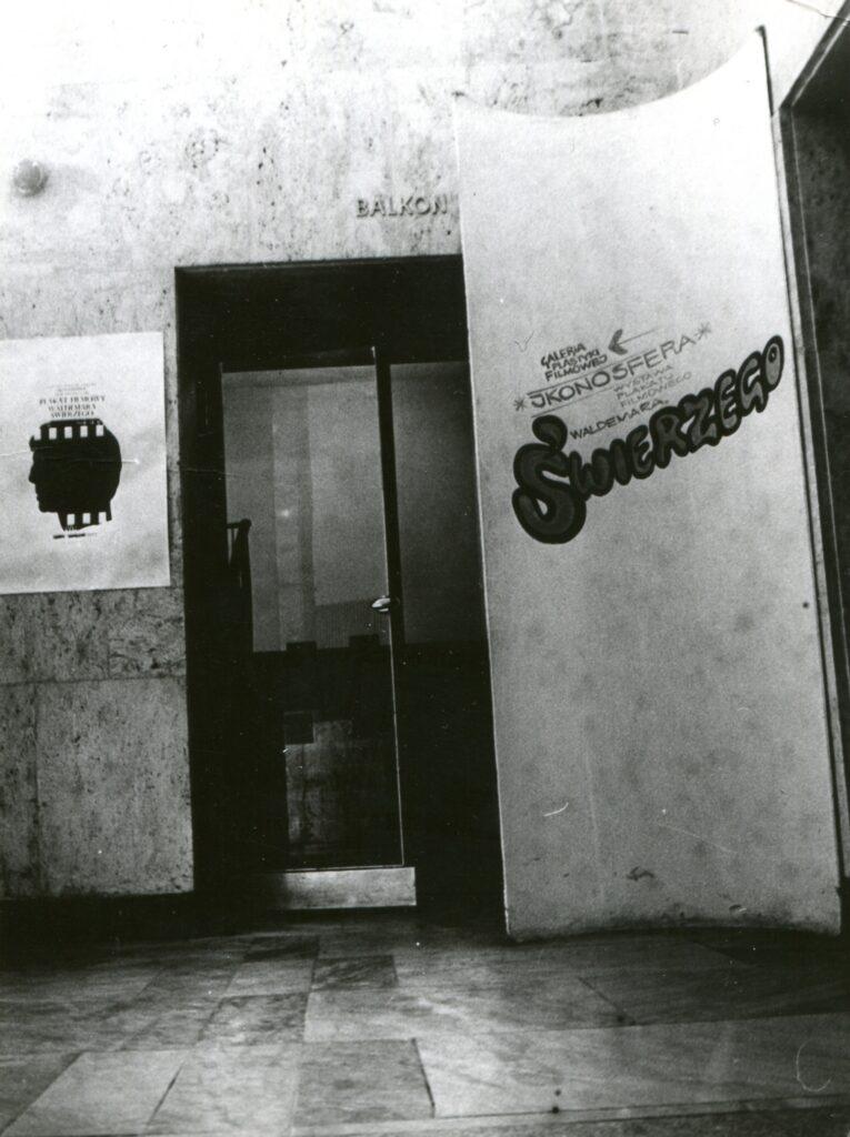 Na czarno-białej fotografii widać wejście do dawnej Ikonosfery - galerii plakatów. Nad wejściem litery BALKON. Po prawej duży roll-up z napisem: GALERIA PLASTYKI FILMOWEJ IKONOSFERA. WYSTAWA PLAKATU FILMOWEGO WALDEMARA ŚWIERZEGO.