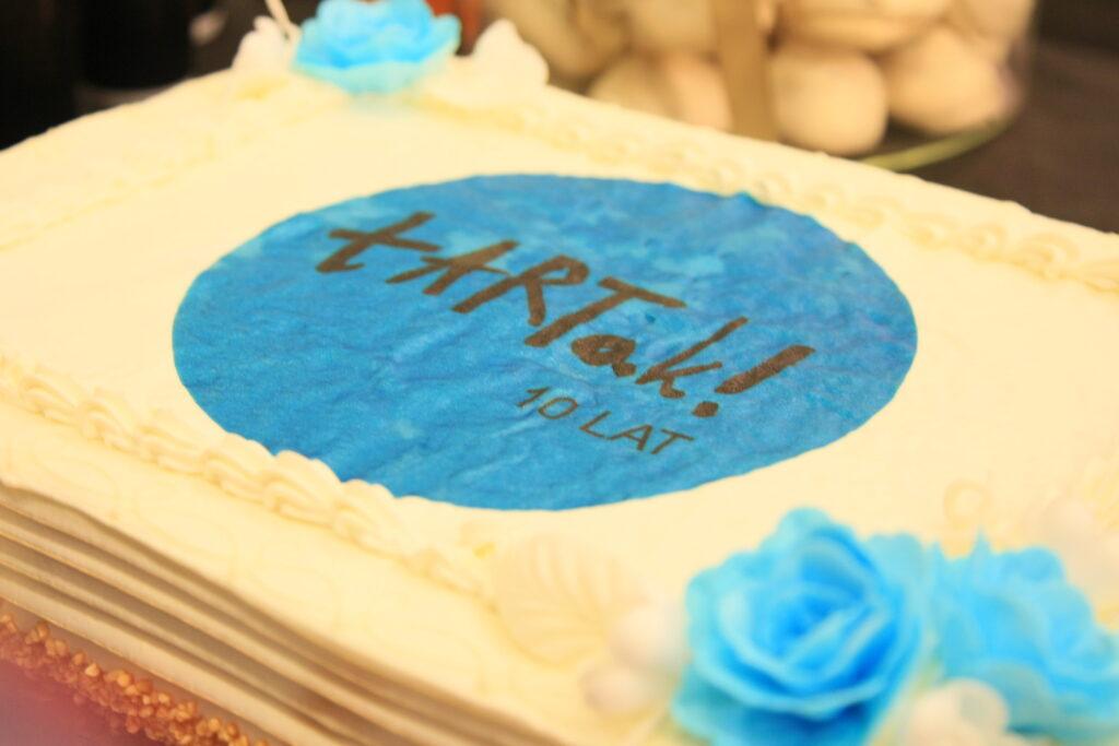 """Na zdjęciu duży, kwatratowy, jubileuszowy tort polany żółtym lukrem. Na środku tortu wykonano koło z niebieskiego lukru, na którym widnieje napis: """" tARTak 10 lat"""". Fotografia została wykonana podczas wernisażu wystawy prac naszych uczestników, która podsumowywała 10. rok działań Pracowni Plastycznej tARTak."""