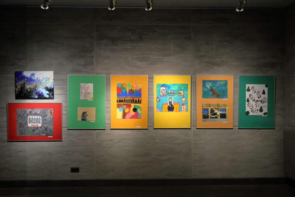 Na fotografii widać dziewięć prac uczestników Pracowni eksponowanych w sześciu ramach oraz jedną pracę wykonaną na blejtramie.