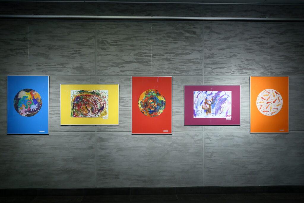 Na ścianie wisi pięć prac uczestników Pracowni. Trzy pionowe z namalowanymi kolorowymi kołami oraz dwie poziome – jedna przedstawia barwną abstrakcję, a druga psa.