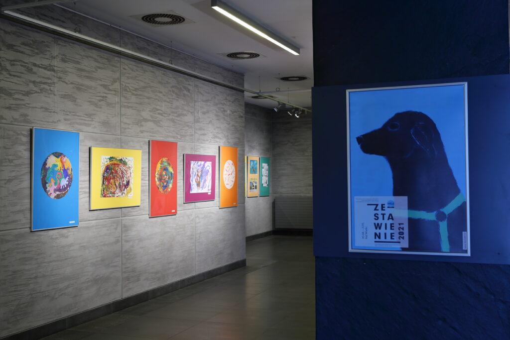 """Po lewej stronie zdjęcia widać pięć prac uczestników Pracowni. Trzy pionowe z namalowanymi kolorowymi kołami oraz dwie poziome – jedna przedstawia barwną abstrakcję, a druga psa. W oddali można dostrzec kolejne dwie prace, ale nie widać, co jest na nich namalowane. Po prawej stronie zdjęcia znajduje się plakat promujący wystawę z napisem: """"Zestawienie 2021""""."""