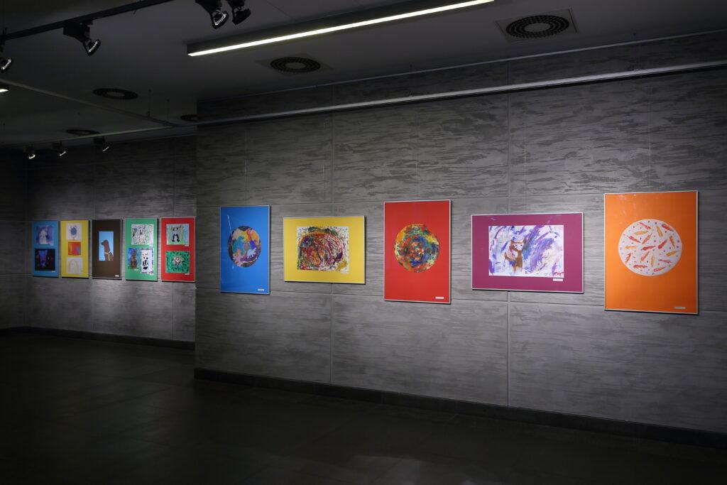Po prawej stronie zdjęcia widać pięć prac uczestników Pracowni. Trzy pionowe z namalowanymi kolorowymi kołami oraz dwie poziome – jedna przedstawia barwną abstrakcję, a druga psa. W oddali widać kolejne jedenaście prac, ale nie można rozpoznać, co jest na nich namalowane, z wyjątkiem jednej, która przedstawia psa.