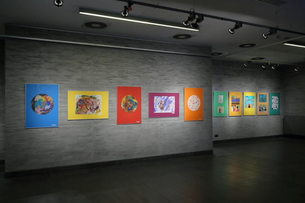 Po lewej stronie zdjęcia widzimy pięć prac uczestników Pracowni. Trzy pionowe z namalowanymi kolorowymi kołami oraz dwie poziome – jedna przedstawia barwną abstrakcję, a druga psa. W oddali widać kolejne siedem prace, ale to, co zostało na nich namalowane, jest niewyraźne.