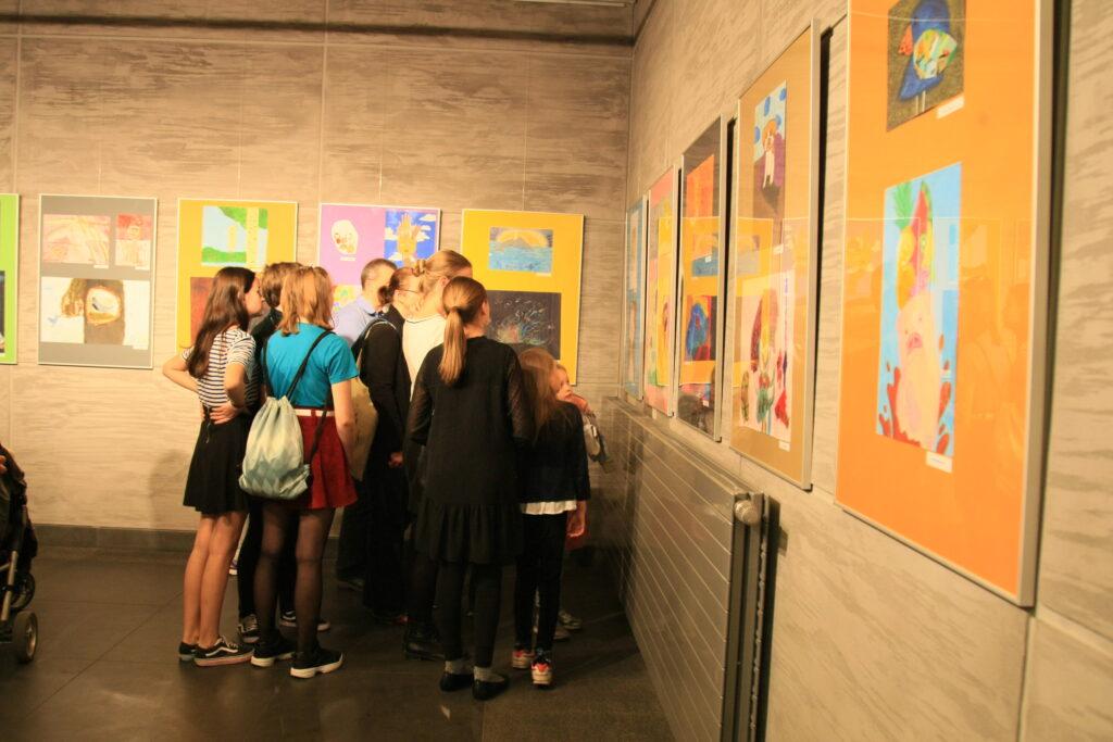Na zdjęciu widać grupę dziewięciu osób, które przyglądają się pracom powieszonym na ścianach w dziewięciu ramach.