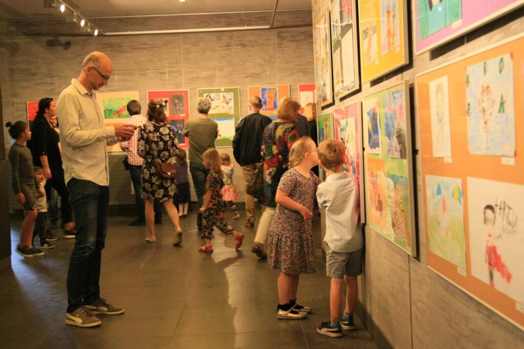 Na zdjęciu widać kilkanaście osób w różnym wieku, które oglądają prace powieszone na ścianie. Prac jest bardzo dużo, czasem umieszczono cztery prace w jednej ramie. Zdjęcie jest niewyraźne, nie widać, co przedstawiają obrazy.