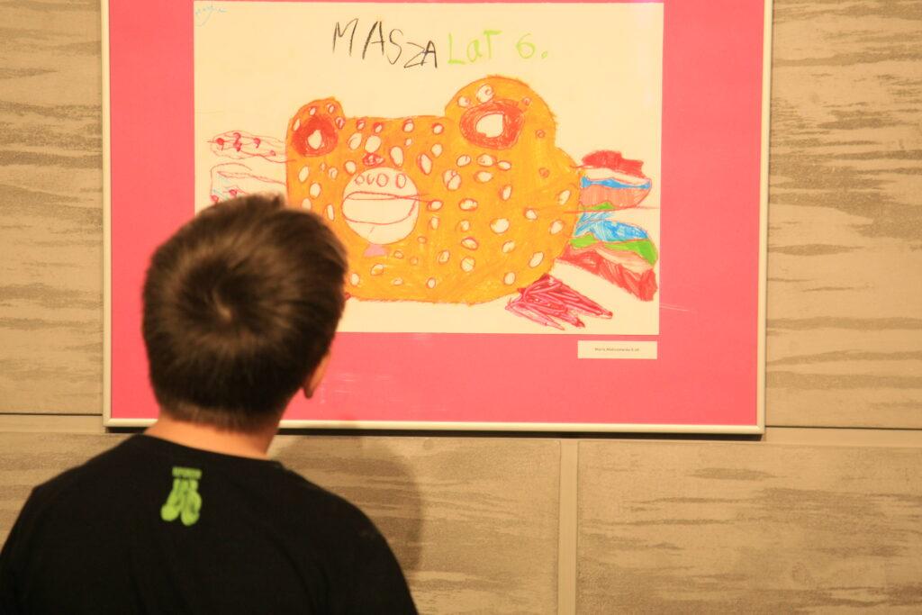 """Na zdjęciu stojący tyłem do obiektywu chłopiec przygląda się pracy, na której widnieje duża kolorowa ryba, a nad nią napis """"Masza lat 6""""."""