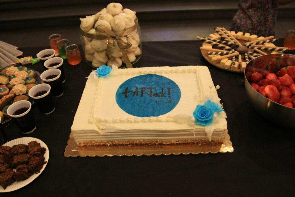 """Zdjęcie przedstawia stół z przygotowanymi na wernisaż przekąskami. W centralnym miejscu znajduje się duży jubileuszowy tort z napisem """"tARTak 10 lat"""". Z lewej strony widzimy: ciasteczka, napoje i szklany pojemnik z bezami, a po prawej: truskawki, czekoladki i waflowe rurki."""