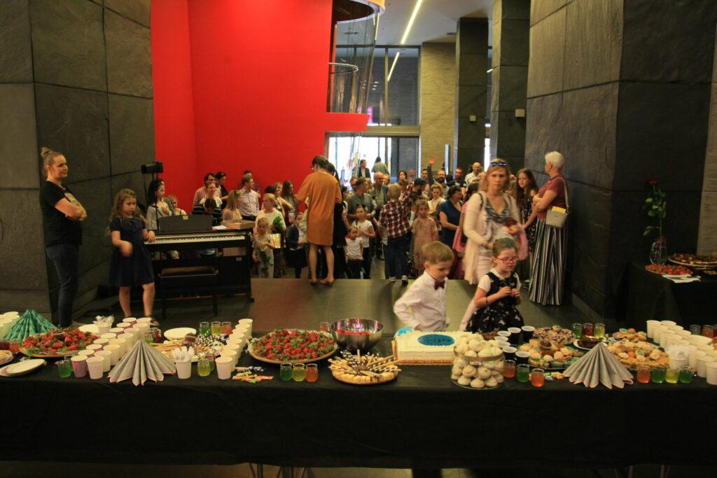 Na pierwszym planie zdjęcia znajduje się długi stół suto zastawiony przekąskami przygotowanymi na wernisaż. Widać na nim tort, dużą ilość ciasteczek i innych słodkości, wiele napojów, truskawki i serwetki. Po lewej stronie, za stołem, stoi pianino, przygotowane do minikoncertu uczestniczki Pracowni. Po środku, tyłem do obiektywu, stoi instruktorka – Sylwia Chudy-Leśnik. W głębi widać tłum ludzi czekających na otwarcie wystawy.