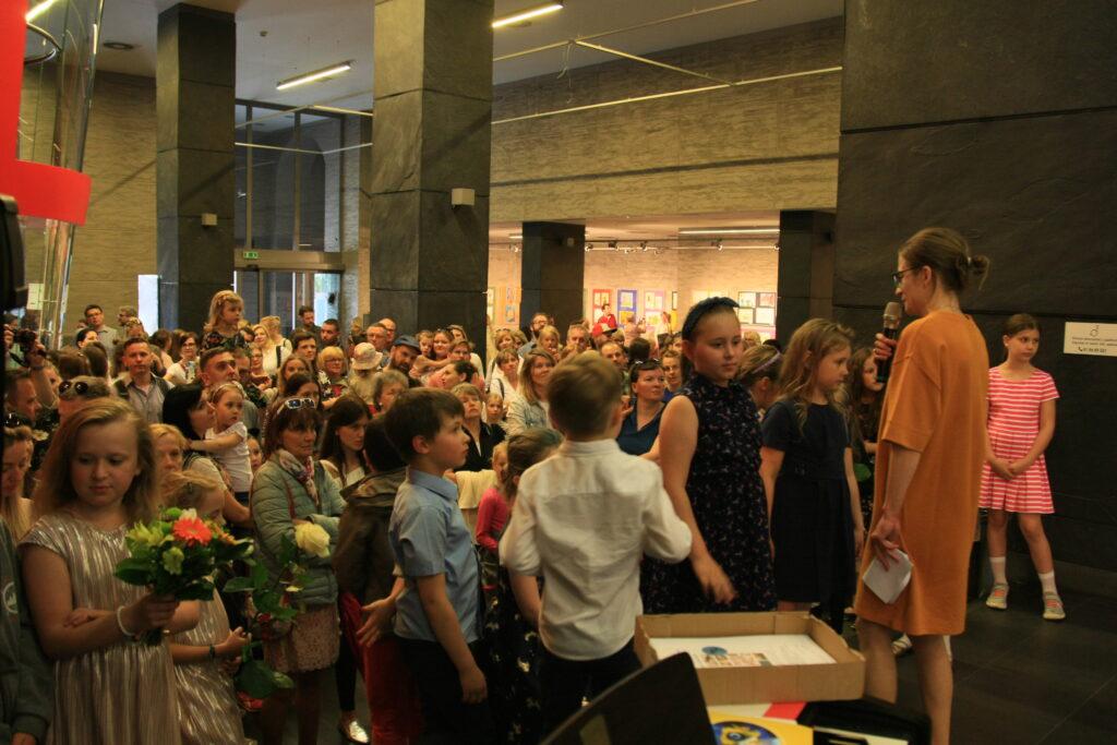 Z prawej strony zdjęcia, zwrócona bokiem do obiektywu, stoi instruktorka – Sylwia Chudy-Leśnik.  Trzymając w ręku mikrofon, otwiera wystawę. Po lewej stronie widzimy tłum ludzi słuchających przemówienia instruktorki.
