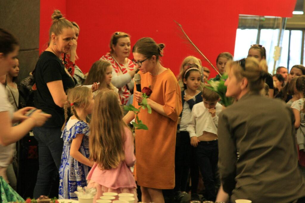 Na środku zdjęcia instruktorka, Sylwia Chudy-Leśnik, rozmawia z dziewczynką. Jest otoczona gromadką dzieci – uczestników Pracowni.